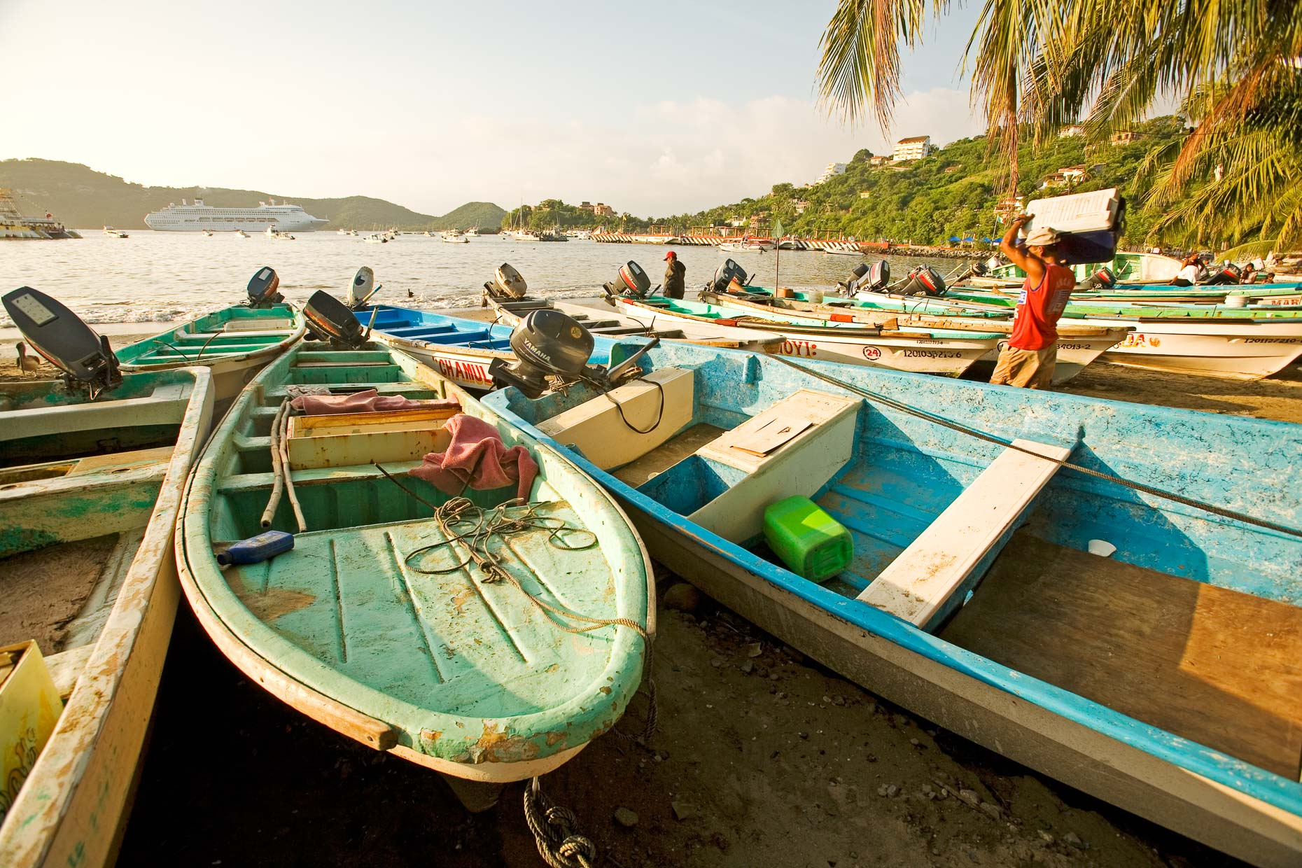 Colorful fishing boats on beach of Zihuatanejo with bay in background and cruise ship in harbor by David Zaitz