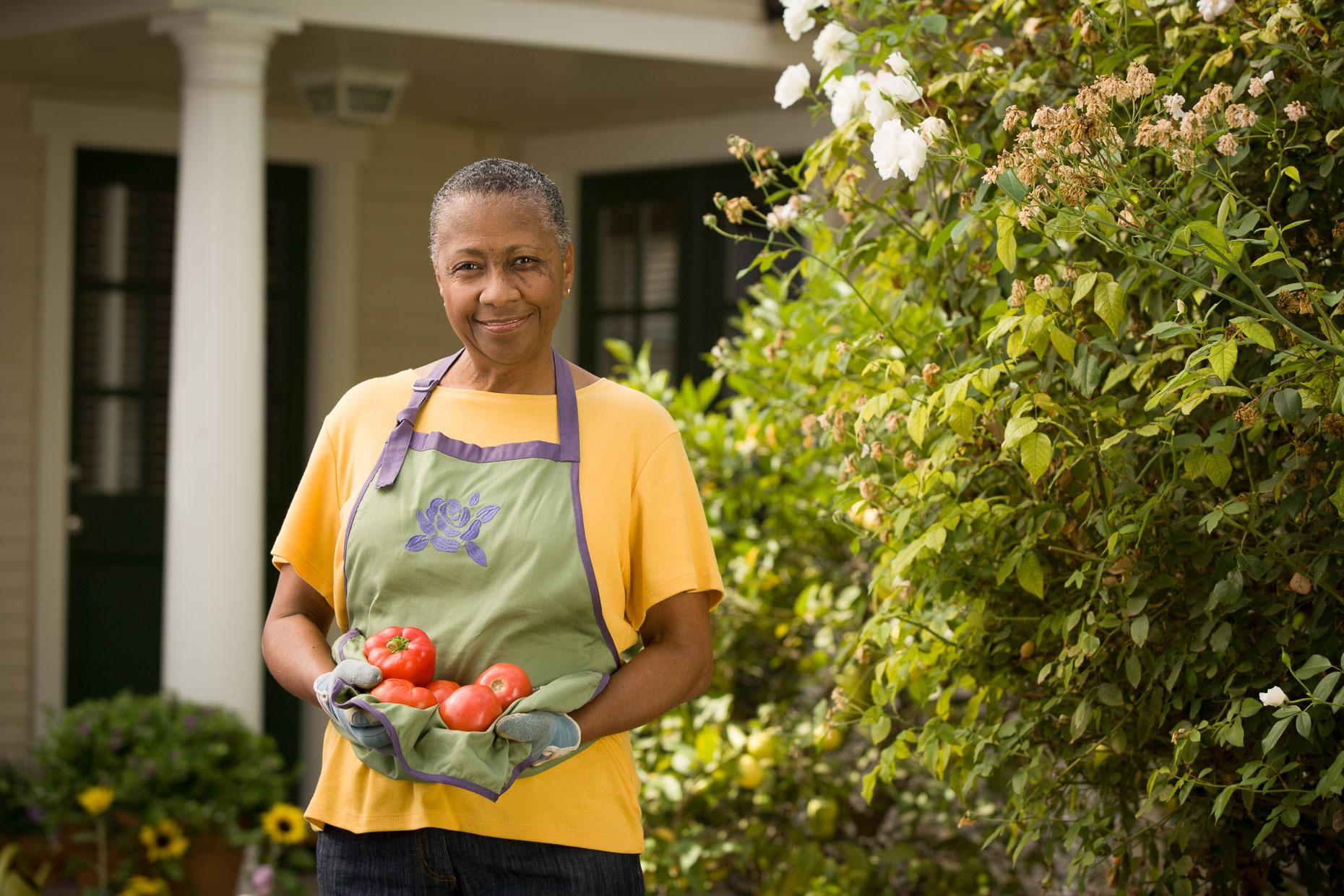 Environmental portrait of African American woman holding tomatoes and bell peppers standing in her backyard garden by David Zaitz