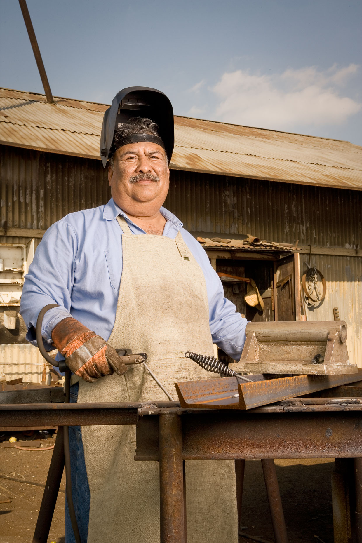 Environmental portrait of welder worker in iron works setting by David Zaitz