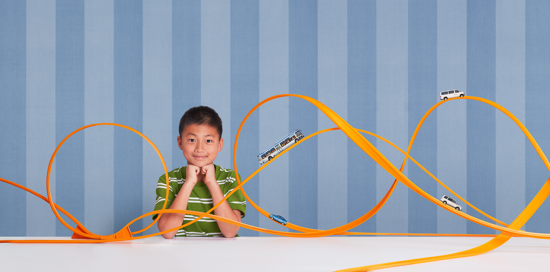 Portrait of Asian boy proud of his complex Hot Wheels toy car track setup in front of blue striped wallpaper by David Zaitz