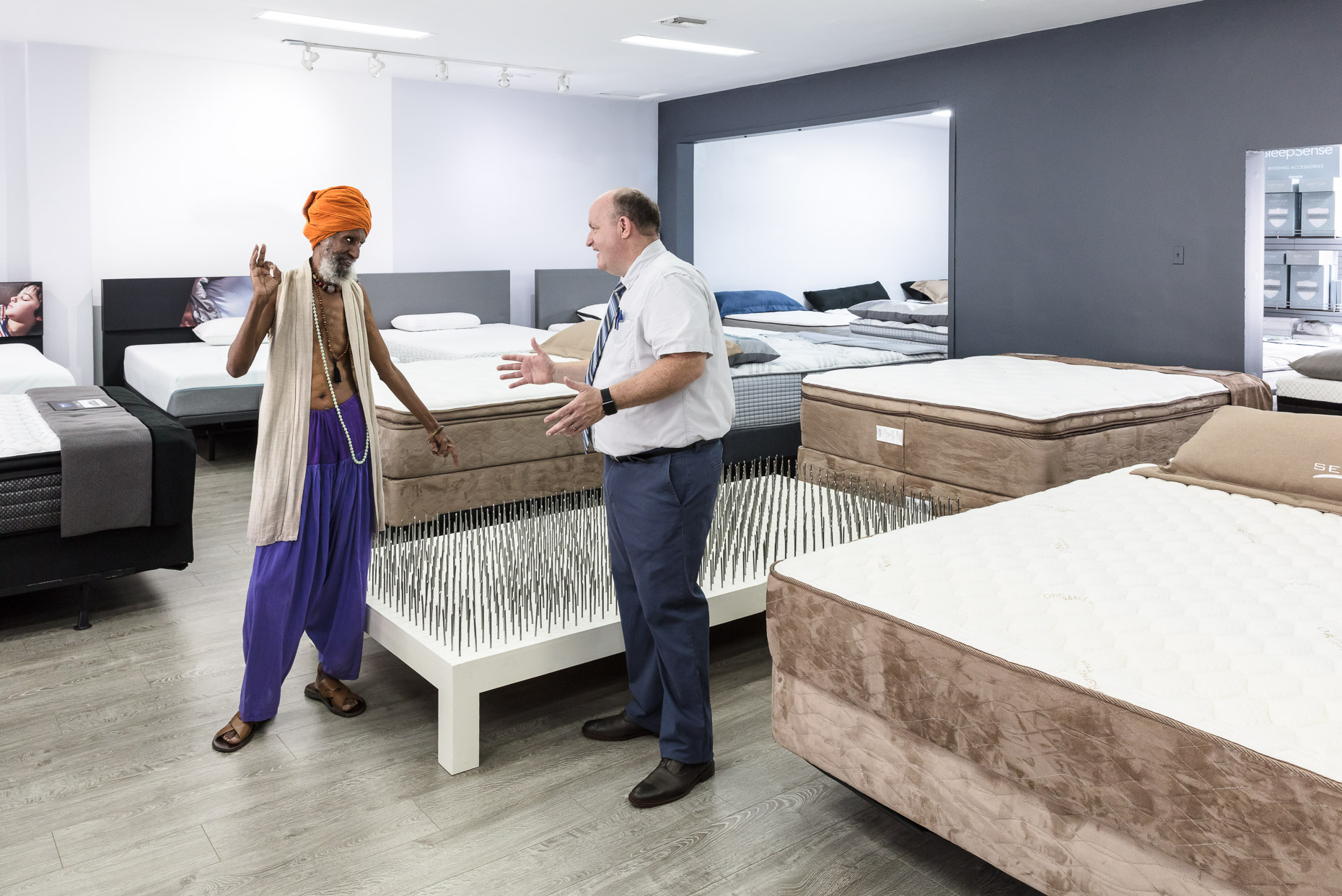 Fakir/Swami/Indian man shopping for bed of nails in mattress store by David Zaitz