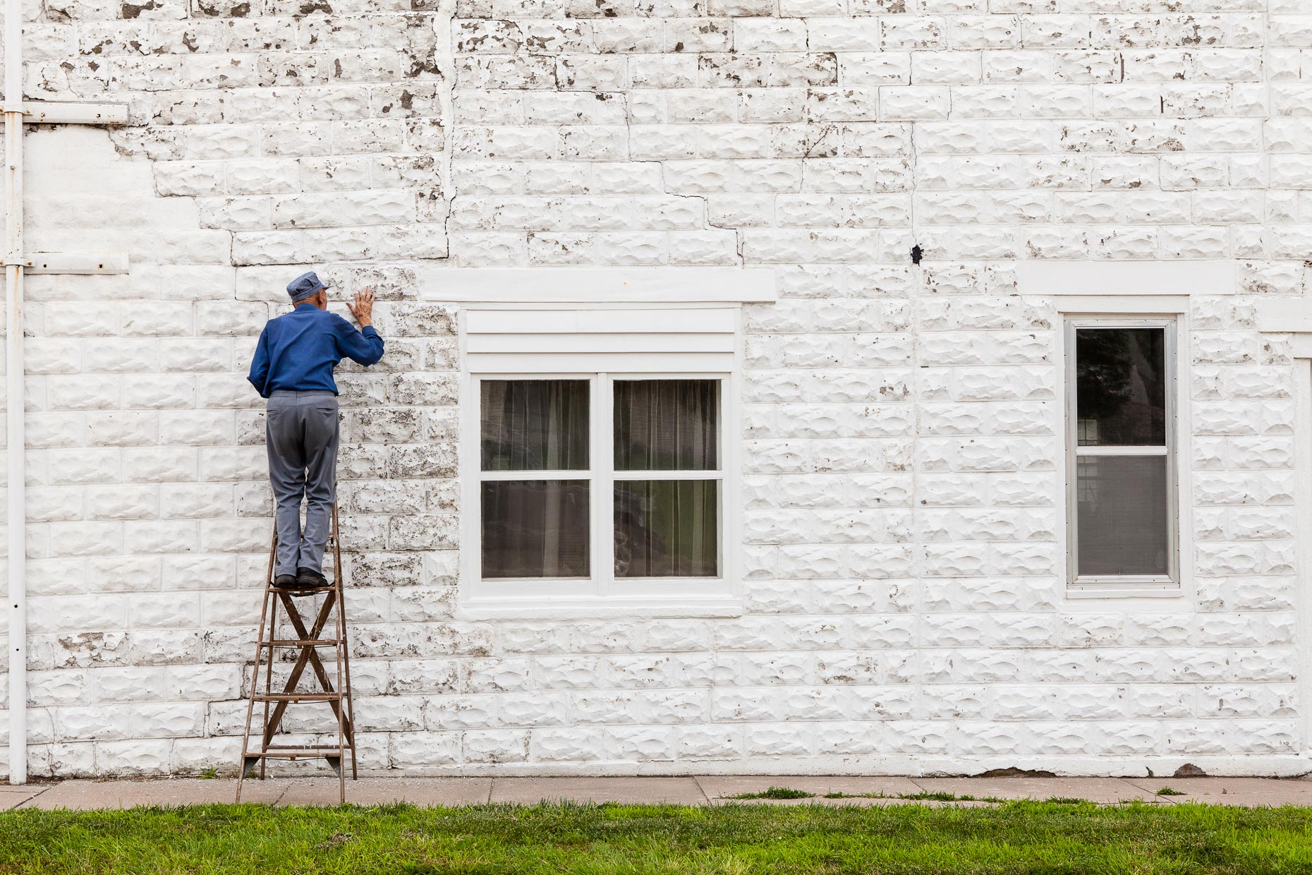 Old man standing on ladder repairs cracks in white brick wall by David Zaitz