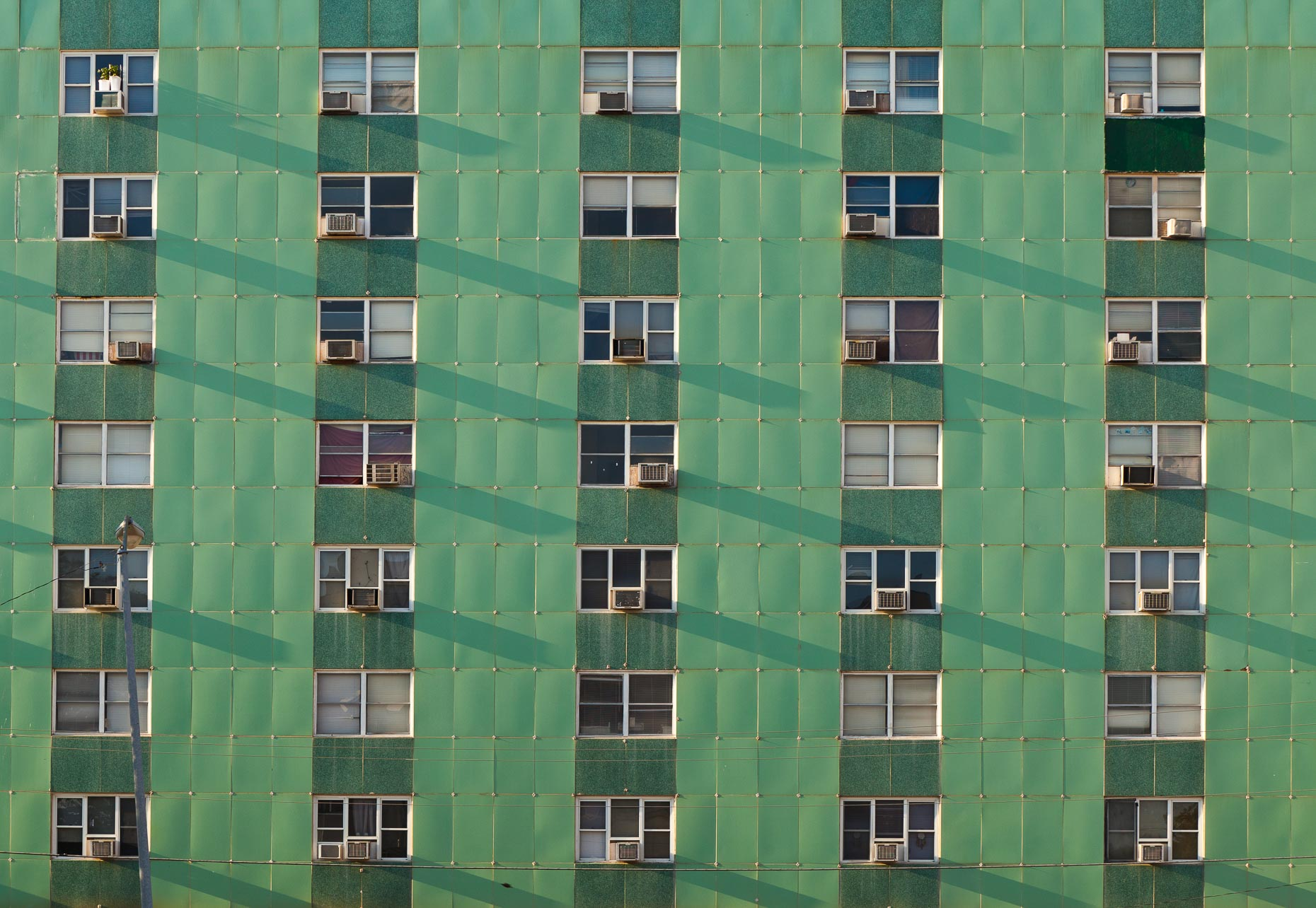Green apartment building with windows and air conditioners by David Zaitz