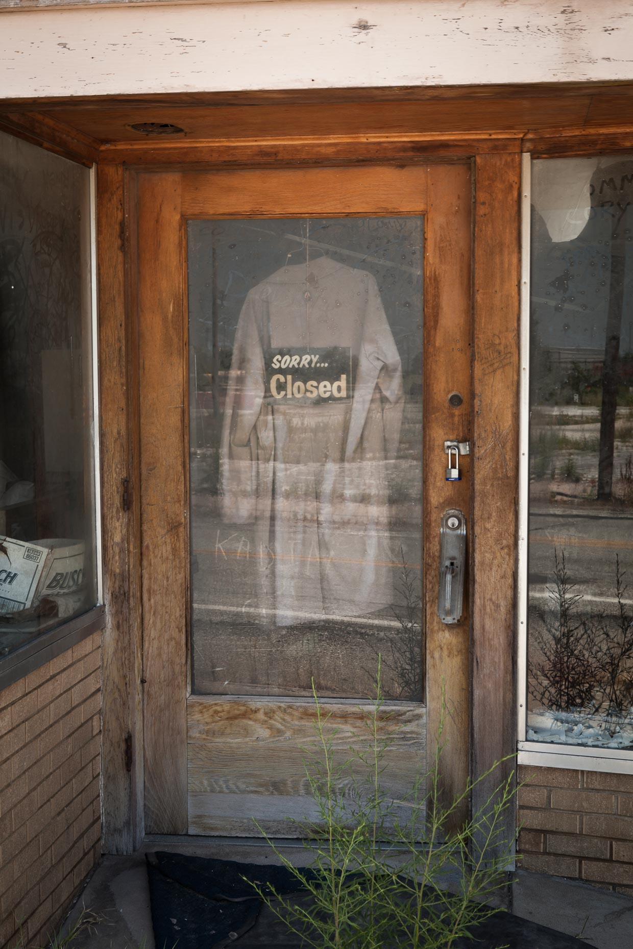 SORRY CLOSED sign in window of store door with clothing hanging by David Zaitz.