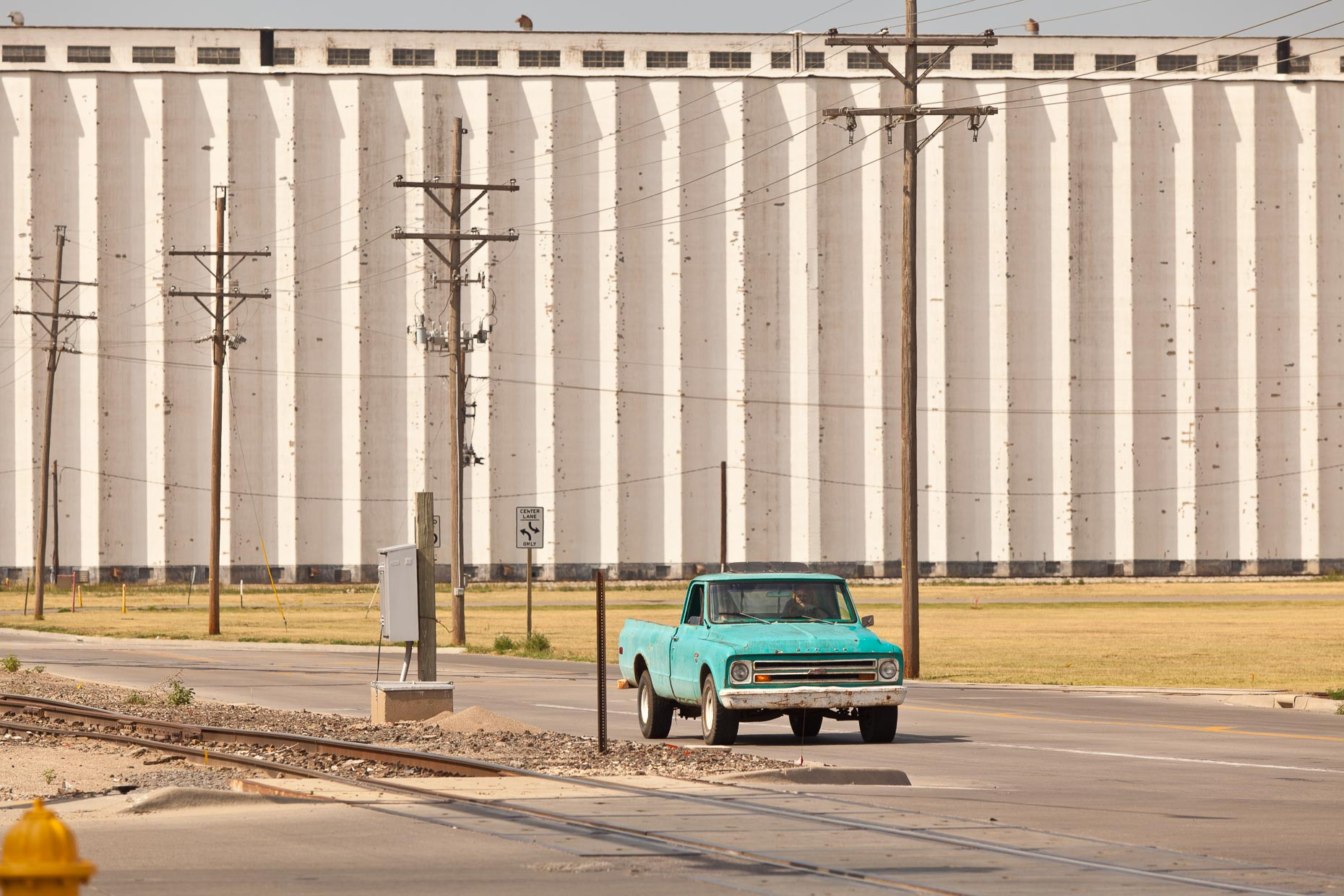 Green pickup truck driving on road with grain elevators in background by David Zaitz