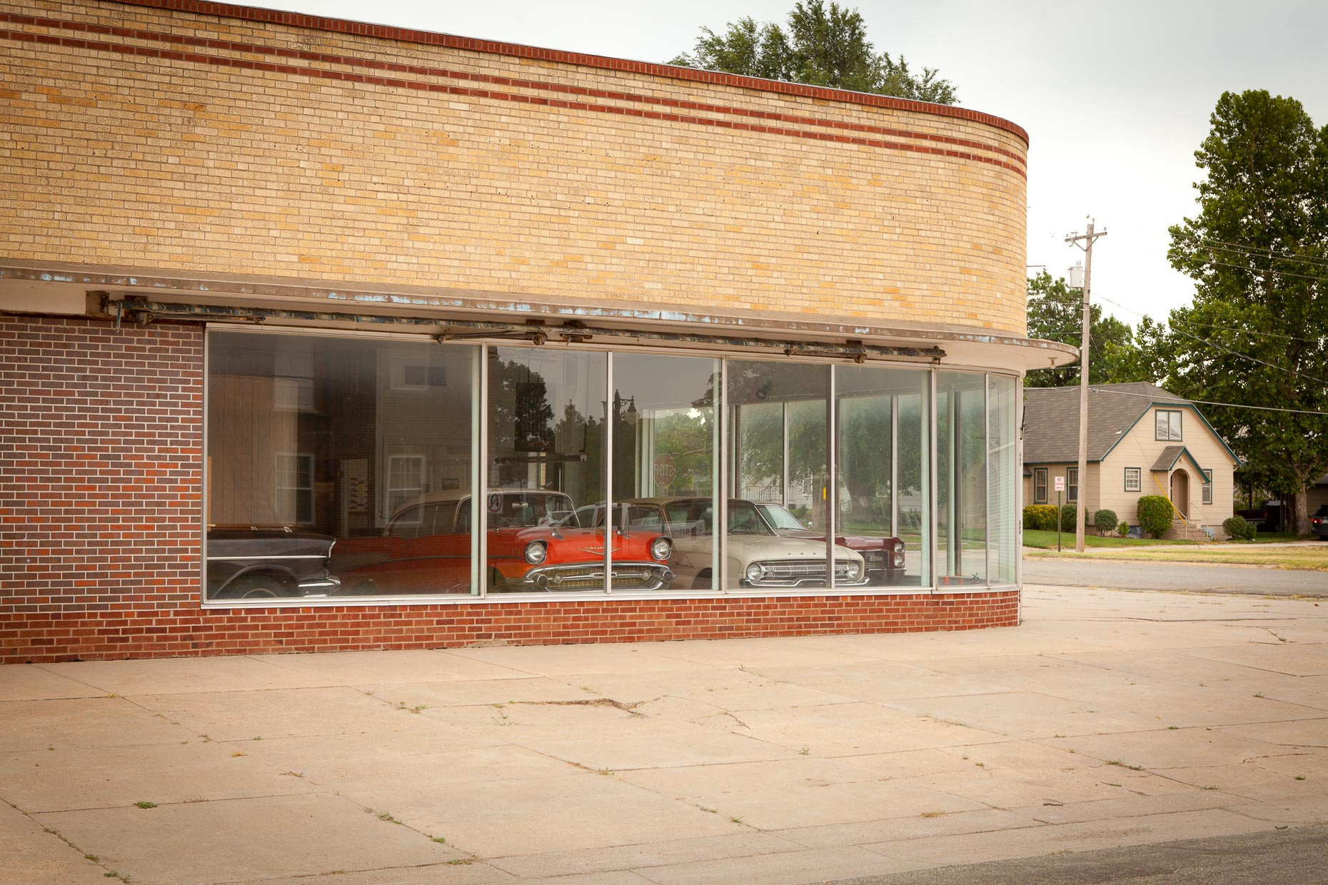 Cars in brick building showroom window by David Zaitz