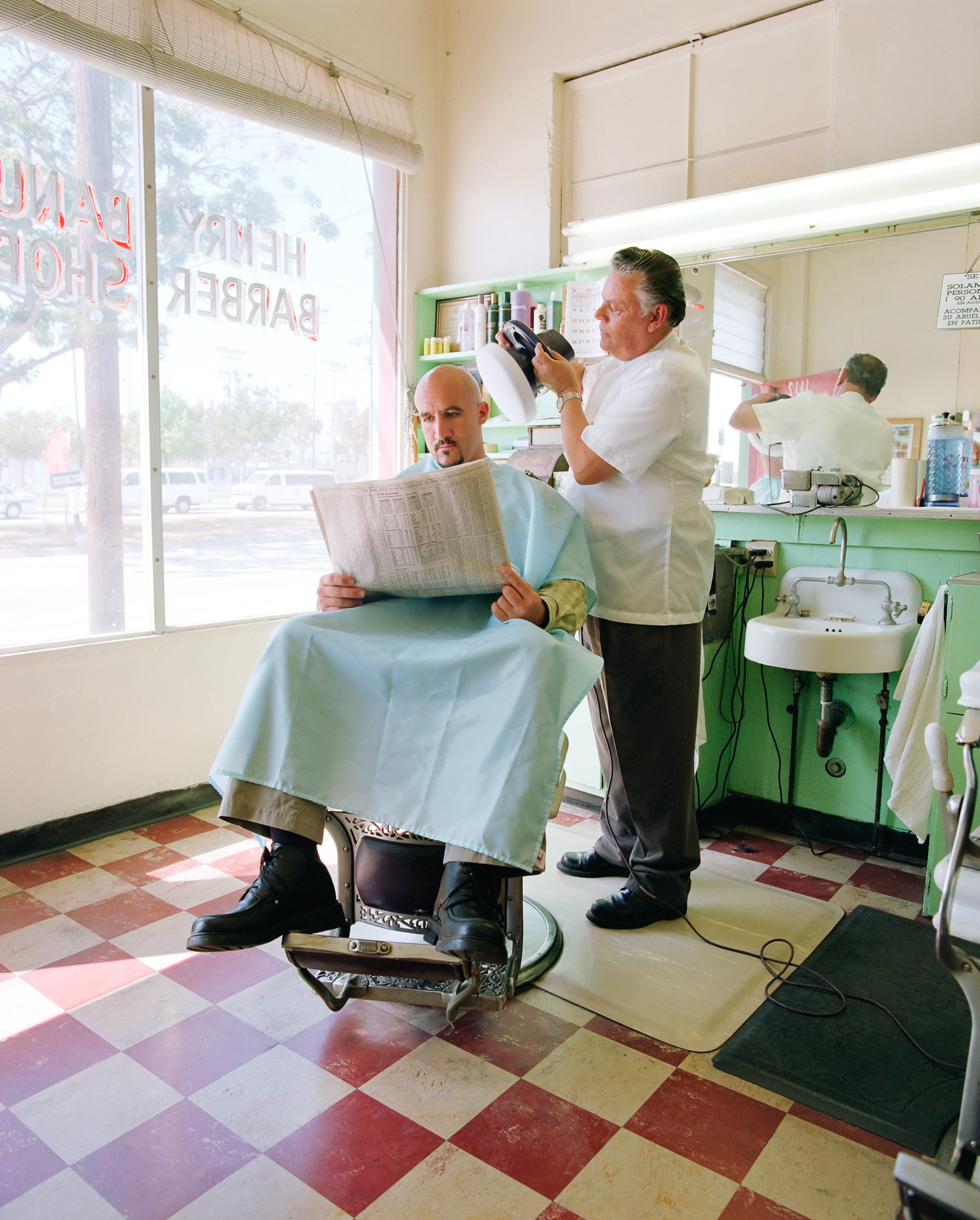 Bald man in barbershop gets his head buffed by barber. David Zaitz.