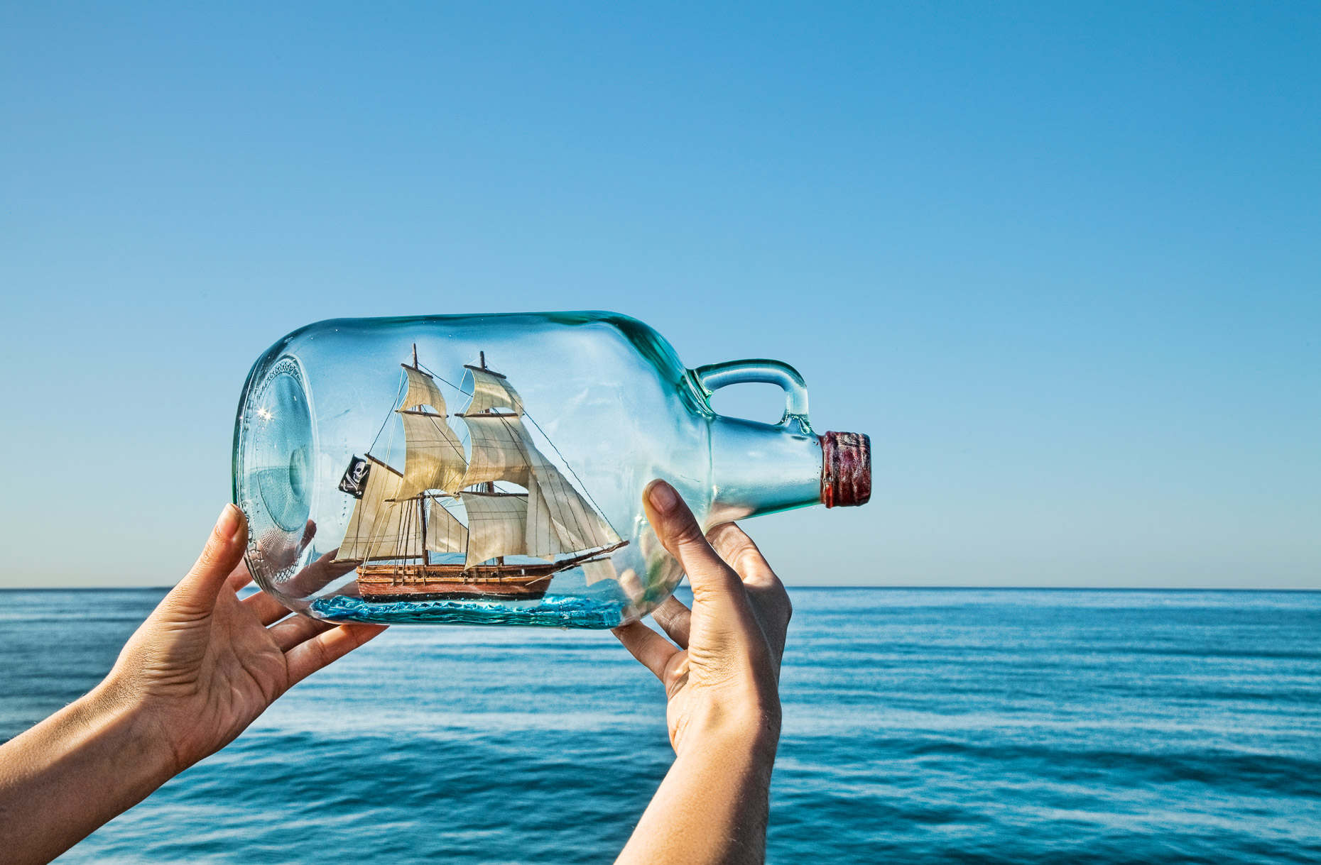 Female hands holding model ship in bottle against ocean horizon.