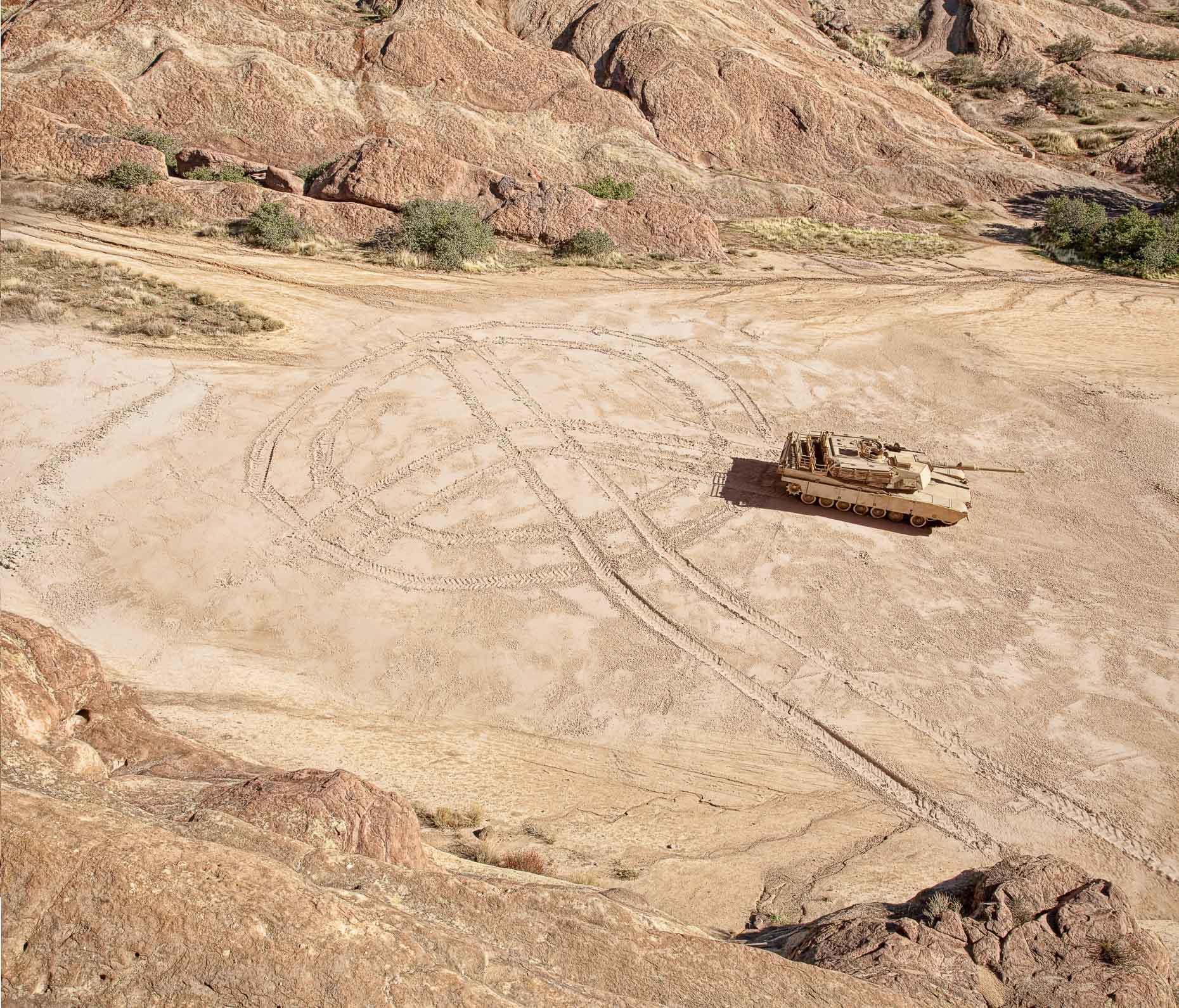 Military tank draws a peace symbol in dirt ground. David Zaitz.