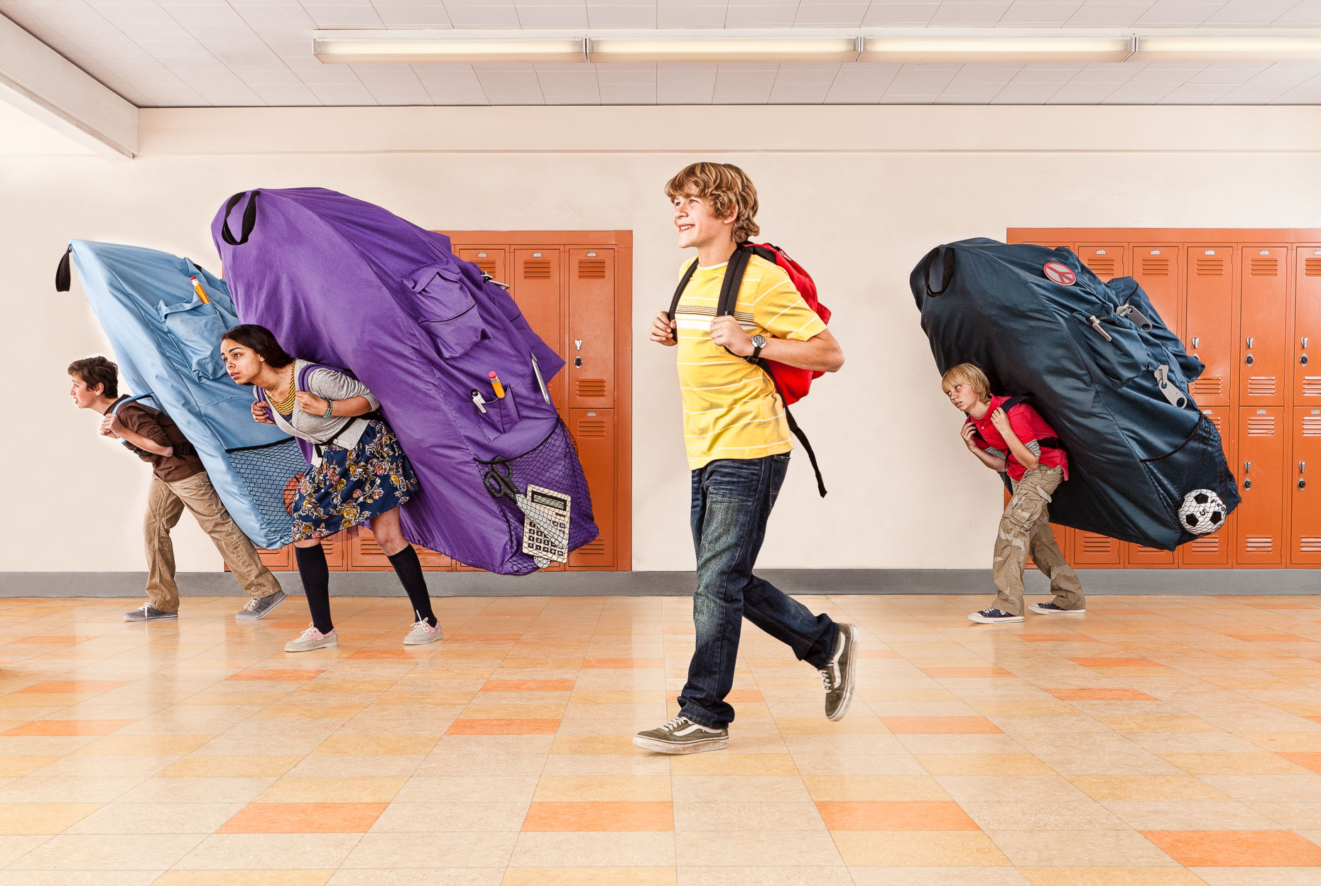 Boy walking in school hallway with backpack, other kids have very large backpacks. David Zaitz.