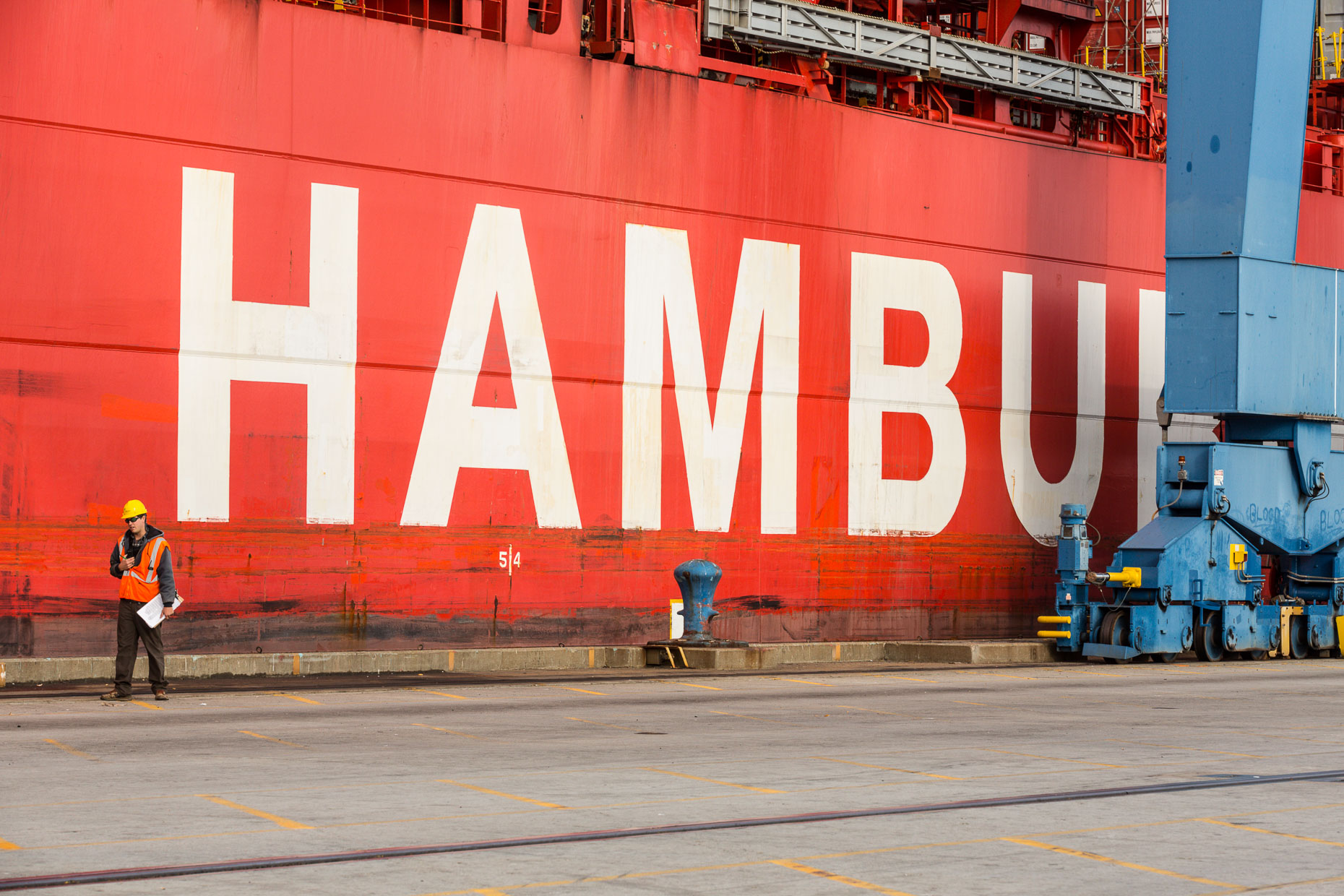 Shipyard working walking past red cargo ship with letters HAMBU in Mt. Pleasant, South Carolina by David Zaitz.