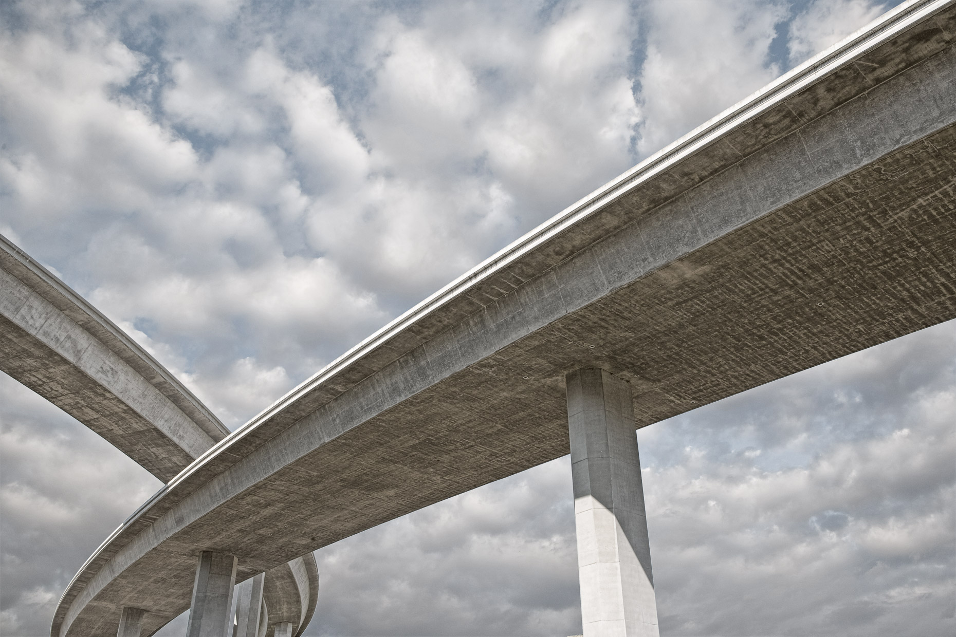 Concrete highway overpasses cross with cloudy sky background. David Zaitz Photography.