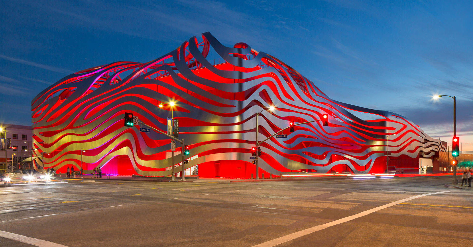 Modern architecture building with bands of metal wrapping around building backlighted with red light. Petersen Automotive Museum in Los Angeles, California. David Zaitz Photography.