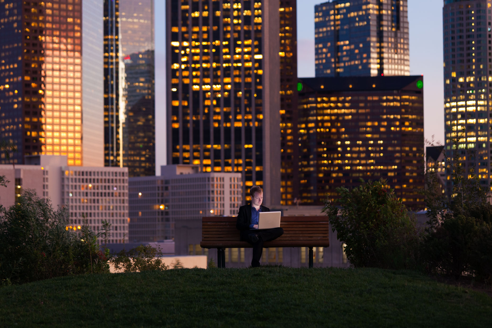 Businessman working on laptop while sitting on park bench with Los Angeles skyline in background at dusk by David Zaitz.