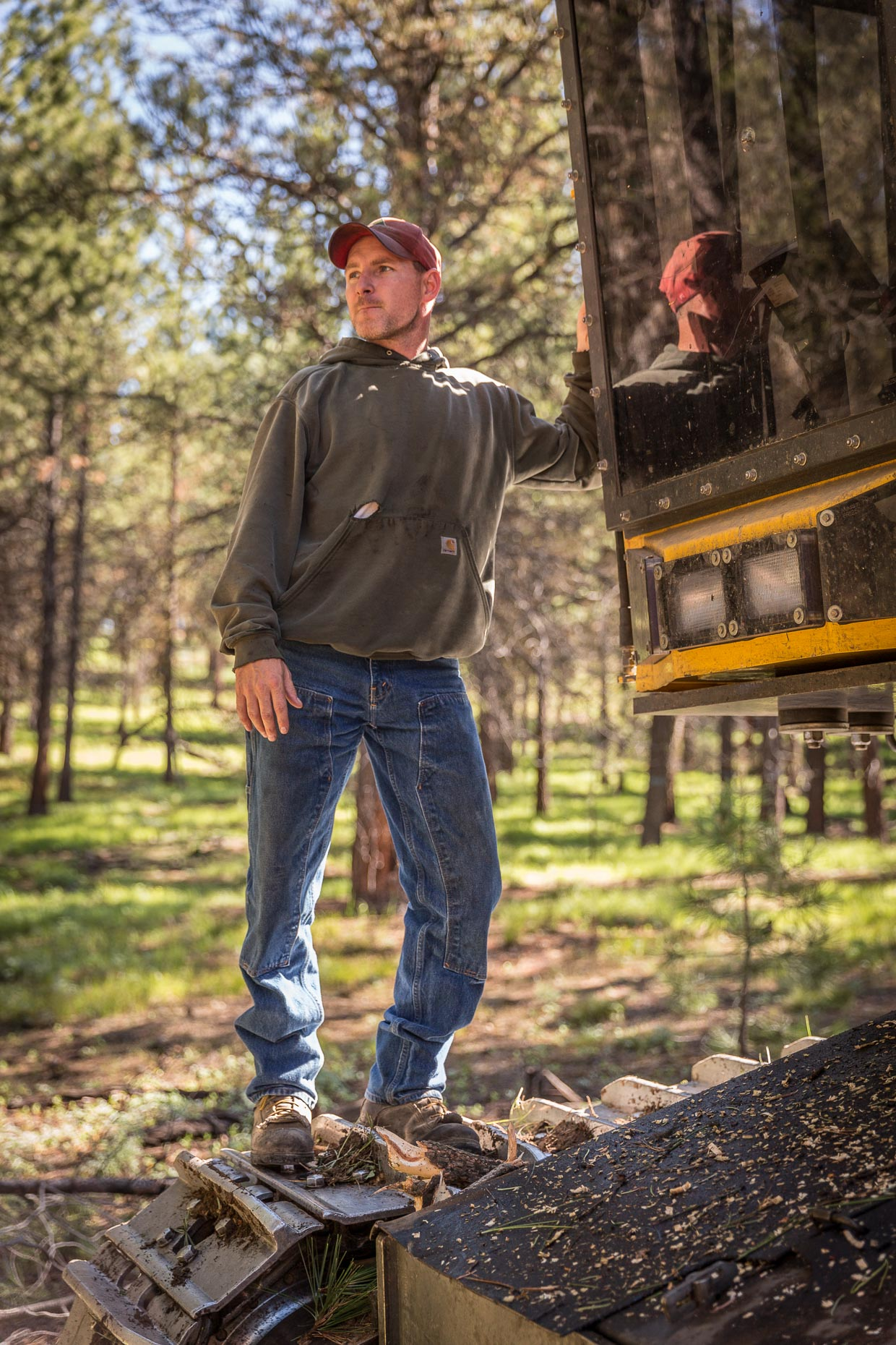 Environmental portrait of man working logging operation in Oregon standing on tree cutting machine, by David Zaitz