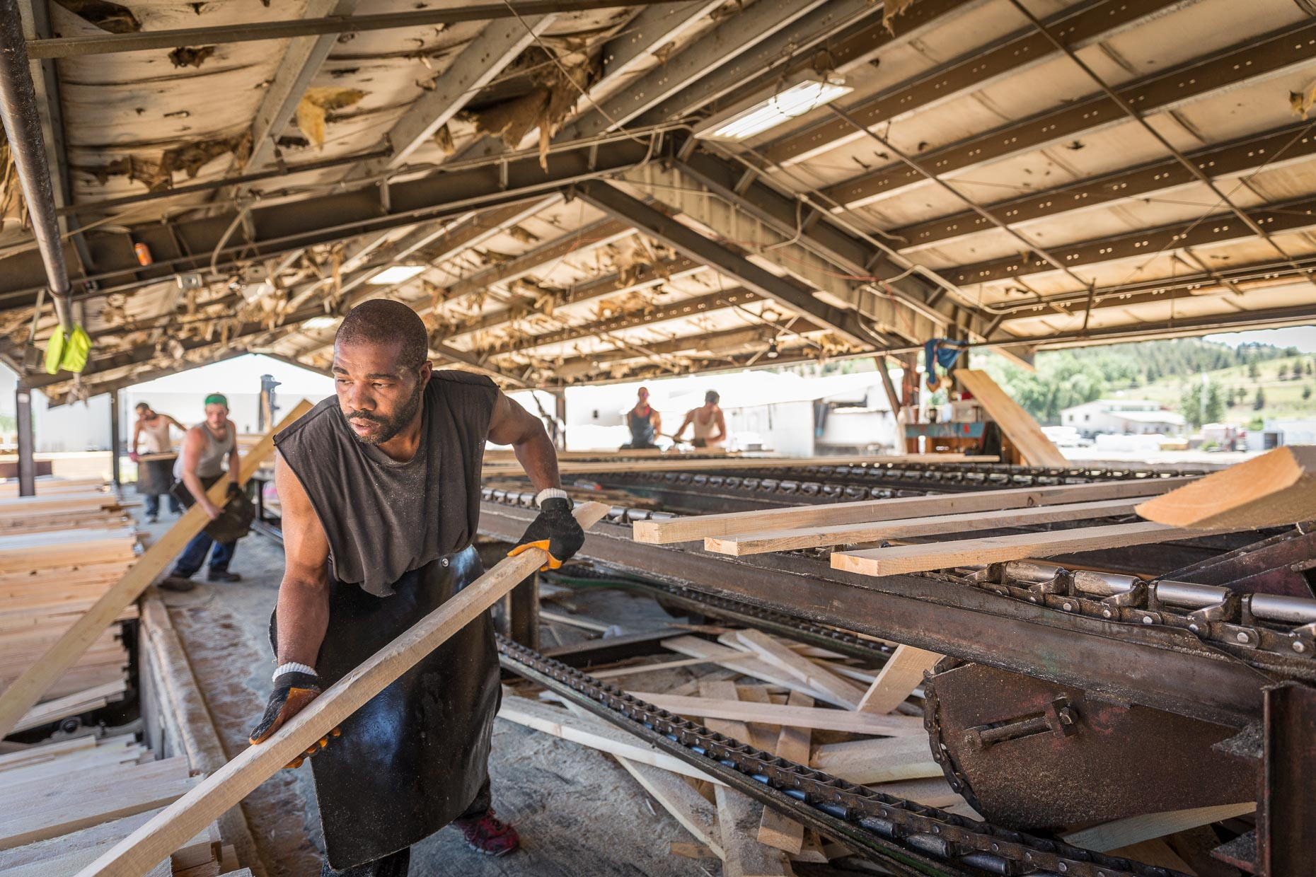 African American male sorting cut lumber, Malheur Lumber Company mill in John Day, Oregon by David Zaitz.
