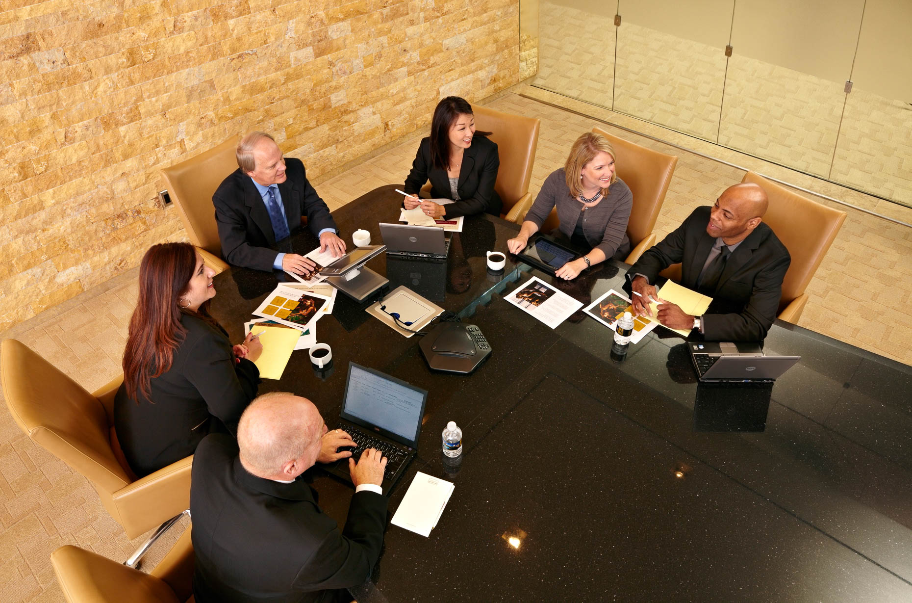 Overhead photograph of people in office meeting in corporate conference room.