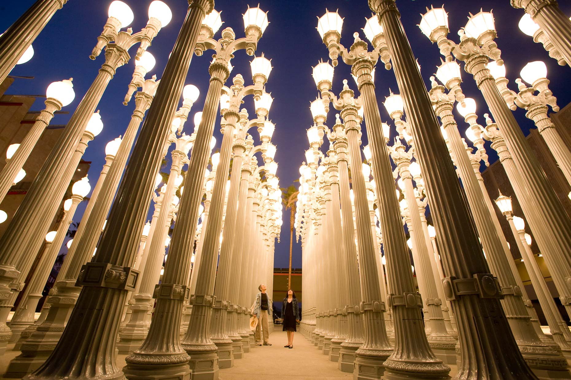 Two women looking at street lights art installation called Urban Lights at LACMA in Los Angeles by David Zaitz