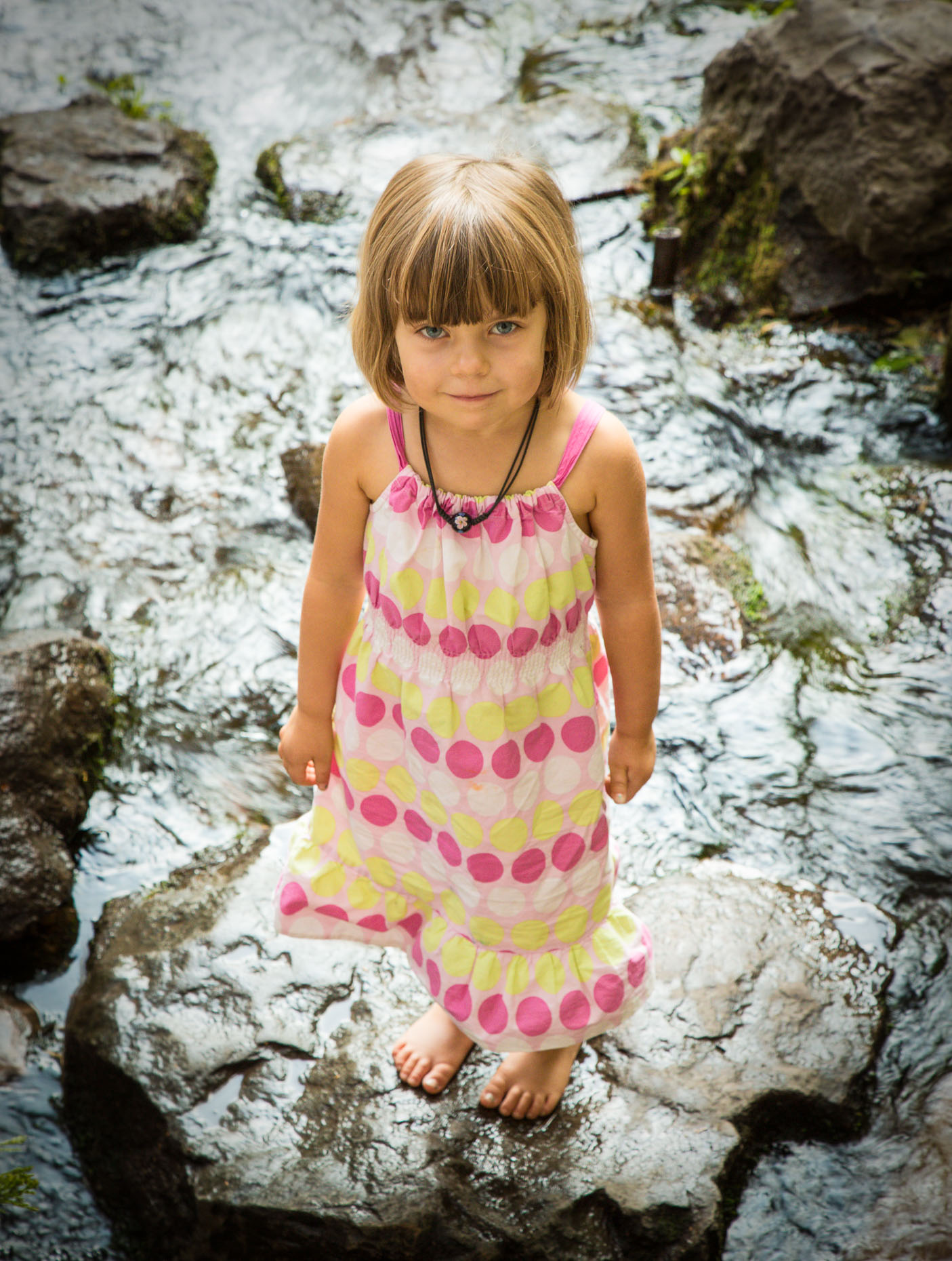 Portrait of little girl in colorful dress standing on rocks in creek in Mt. Shasta City, California by David Zaitz