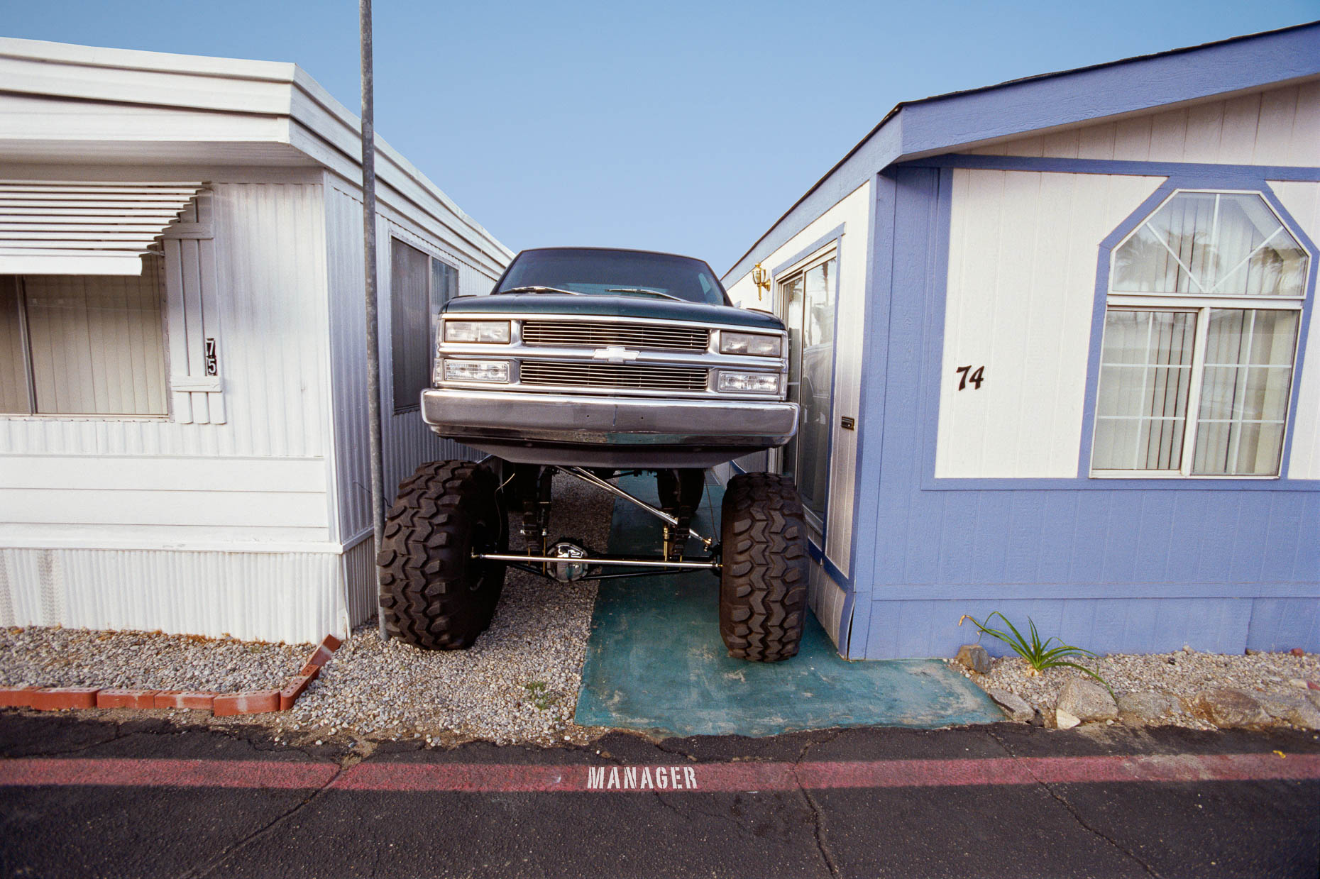 Monster truck parked tightly between two mobile homes. MANAGER is painted on pavement in front of it. David Zaitz