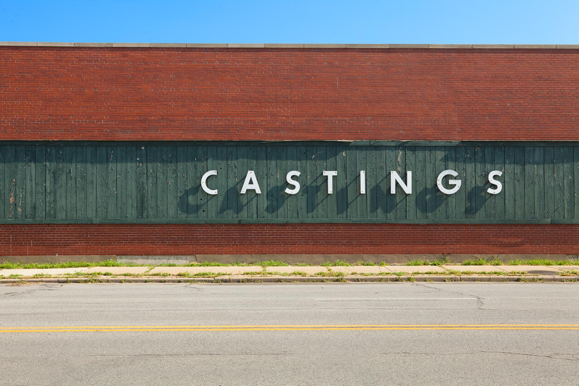 CASTINGS sign on side of green and brick building by David Zaitz