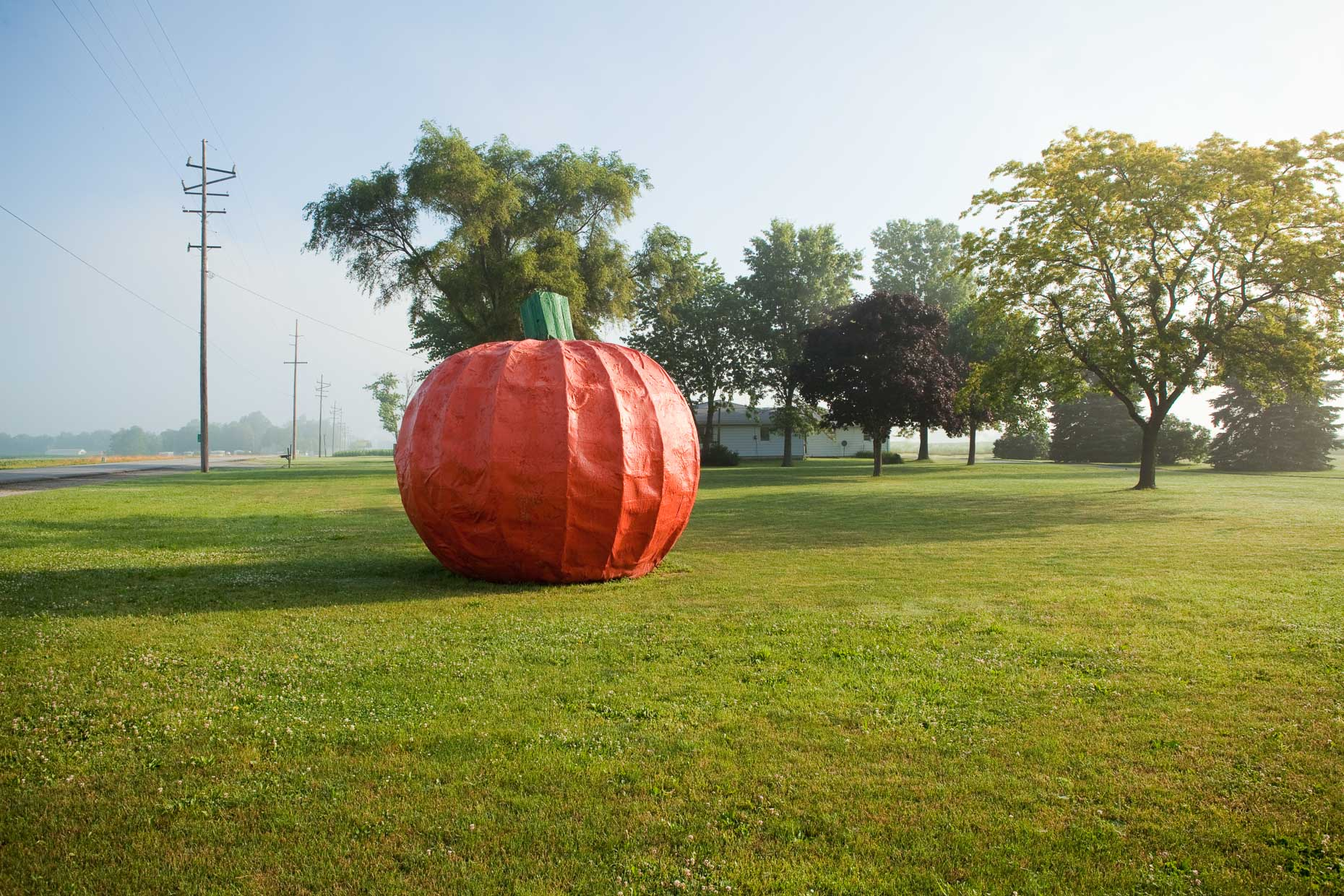 Large fake pumpkin on lawn of farm house by David Zaitz