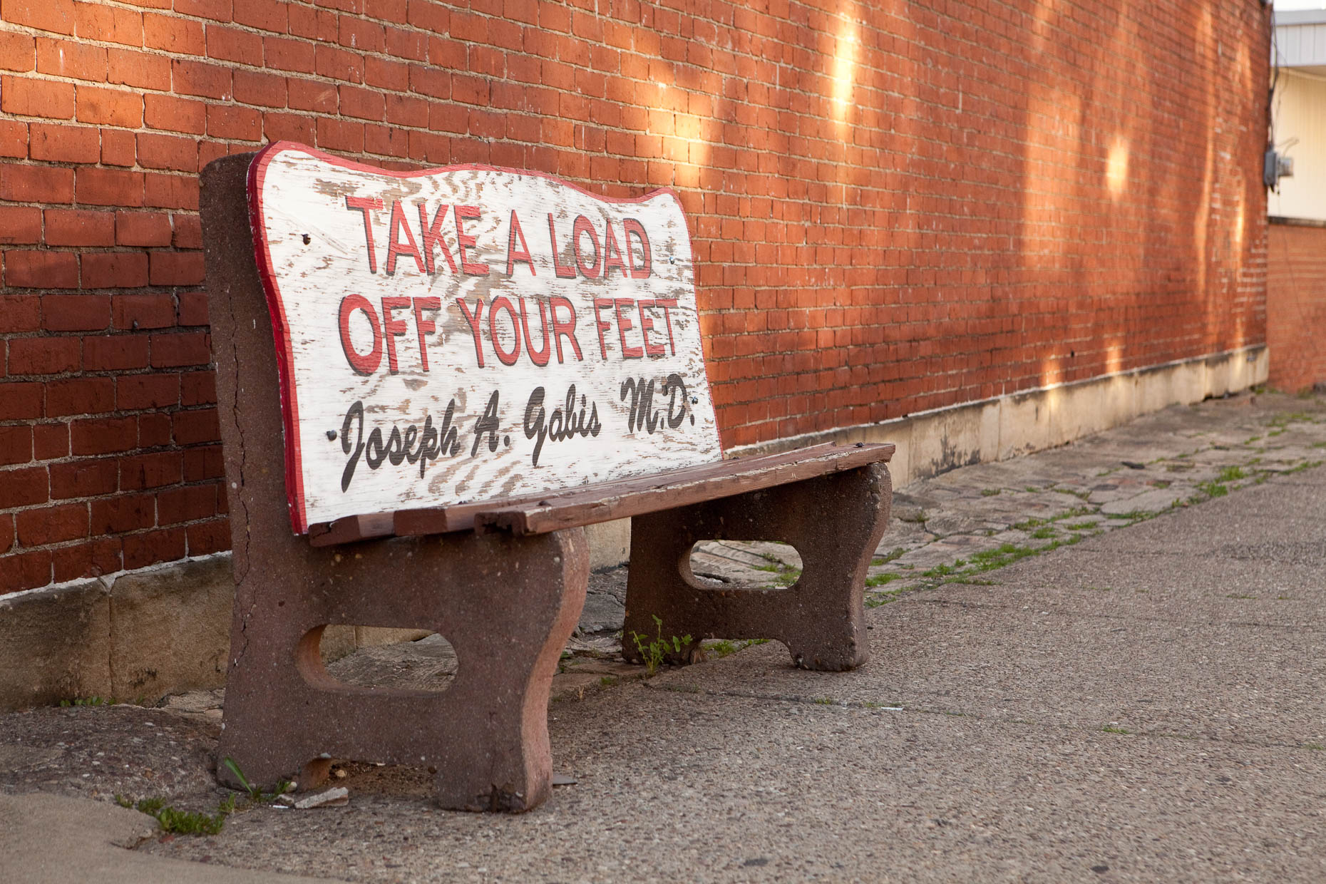 Bus bench with TAKE A LOAD OFF YOUR FEET signage by David Zaitz