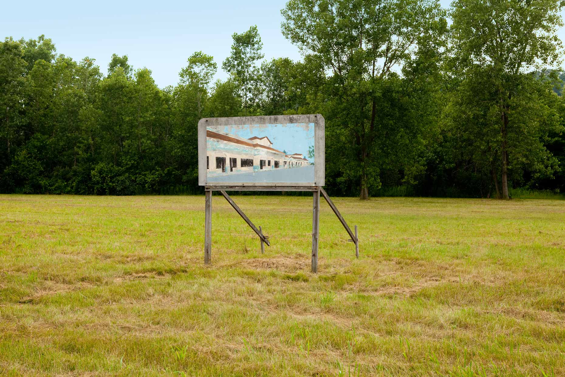 Billboard showing proposed development building on vacant lot.