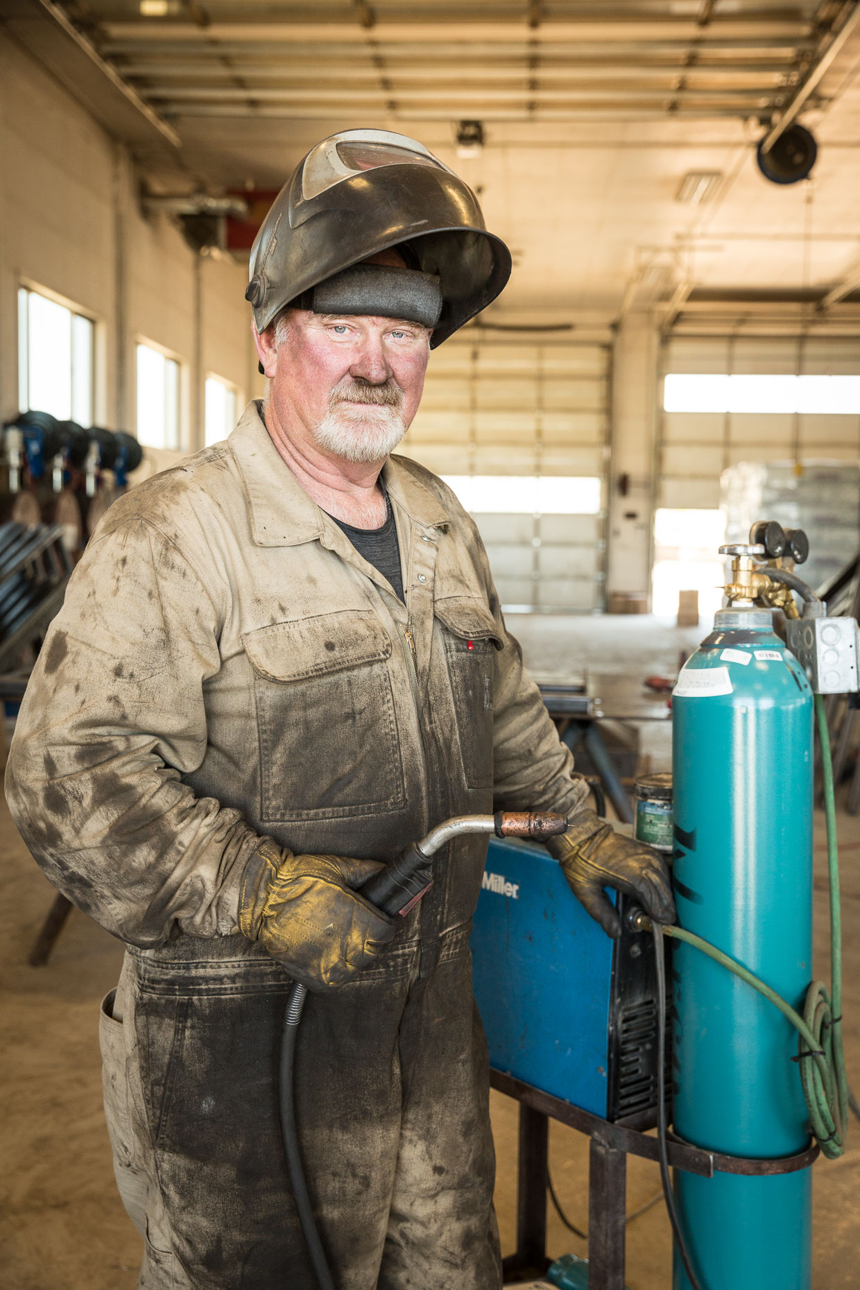 Environmental portrait of welder in workshop.