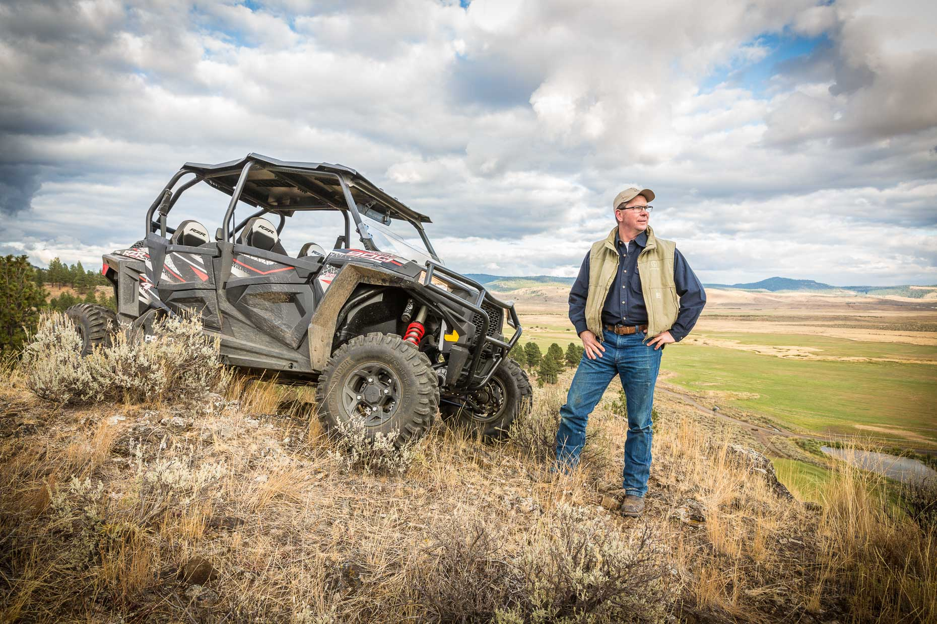 Environmental portrait of man standing next to ATV on top of hill in Seneca, Oregon.
