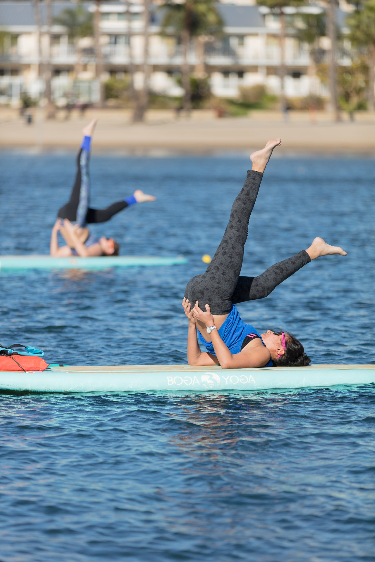 Women practicing yoga will on stand up paddle boards on water in Marina del Rey, California